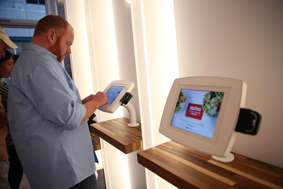 A customer uses an interactive kiosk to place orders at eatsa, a fully automated fast food restaurant in San Francisco.